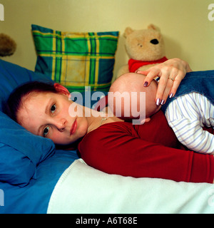 Teenage girl lying on bed with her baby holding the babys head - Stock Photo