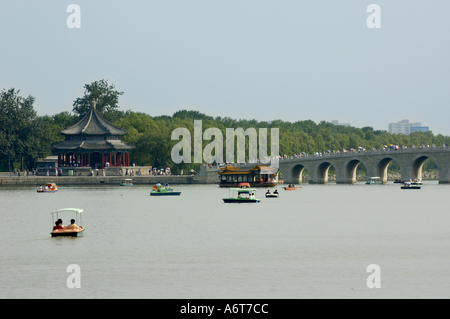 People boating on Kunming Lake near the Seventeen-Arch Bridge, Summer Palace, Beijing, China. - Stock Photo