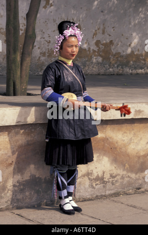 China, Guizhou Province, Guiyang. Miao (Hmong) maiden with 3-string instrument in traditional costume. - Stock Photo
