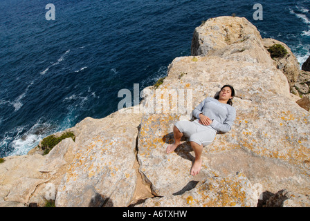 Model Released Fit young brunette relaxed laying down on a mountain in front of the sea Photo by Nano Calvo VWPics - Stock Photo