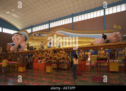 Local young men with mops and buckets clean the huge reclining Buddha at Wat Chayamangkalaram on Penang island Malaysia - Stock Photo