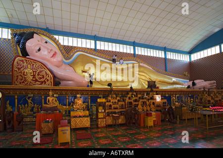 Four local young men with mops clean the huge reclining Buddha at Wat Chayamangkalaram on Penang island Malaysia - Stock Photo