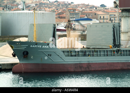 Sete port bulk carrier freighter at dockside during unloading of dusty material possibly sand or grain - Stock Photo