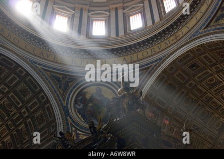 Lightbeams falling through the windows of the dome of Saint Peter's Basilica on the cross of the altar, Vatican, - Stock Photo
