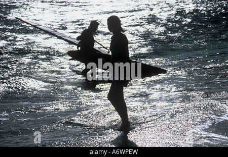 Surfers Surf life male and female young fit windsurf sea ocean beach sport holiday vacation - Stock Photo