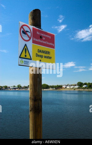 Sign on a post infront of a lake, indicating danger of deep water, and swimming restrictions. - Stock Photo