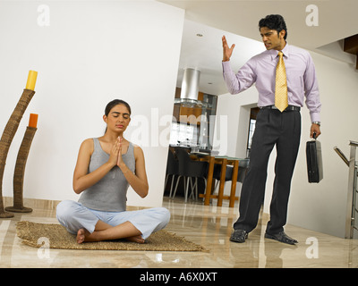 An angry man confronting a meditating woman - Stock Photo