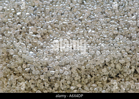 Close-up of a large pile of genuine, uncut diamonds. - Stock Photo