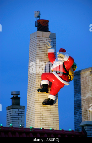Statue of Santa Claus climbing a chimney bearing presents and gifts for Christmas - Stock Photo