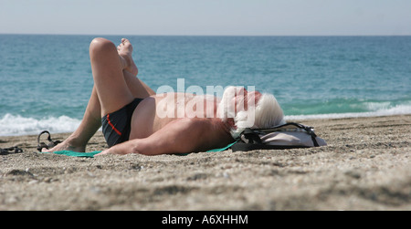 old man sun-bathing on hot beach - Stock Photo
