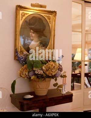 Gilt-framed Edwardian painting with picture light above small antique table with pot of dried flowers - Stock Photo