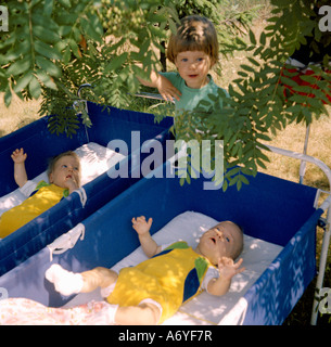 Child standing next to two baby cribs - Stock Photo