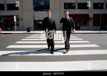 Two businessmen walking over a pedestrian crossing - Stock Photo