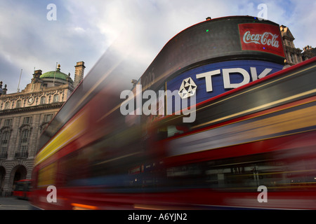 Picadilly Circus, London with bright billboards and two red double decker bus's blurred in foreground. - Stock Photo