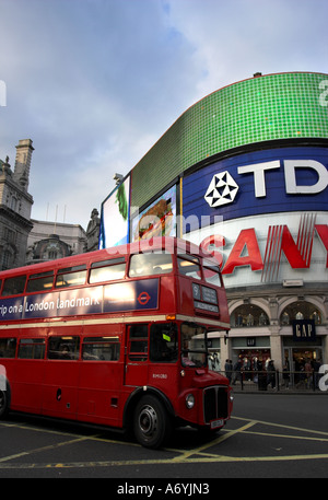 Picadilly Circus, London with bright billboards and old red double decker bus in foreground. - Stock Photo