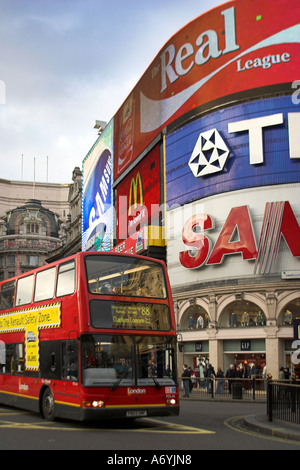 Picadilly Circus, London with bright billboards and red double decker bus in foreground. - Stock Photo