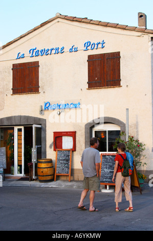 La Taverne du Port with many chalkboards with menus. A couple reading the offers. Marseillan. Languedoc. France. - Stock Photo