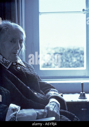 old woman sitting at a window thoughtful - Stock Photo