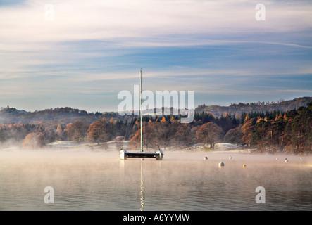 A catamaran moored on a mist covered lake Windermere at sunrise - Stock Photo
