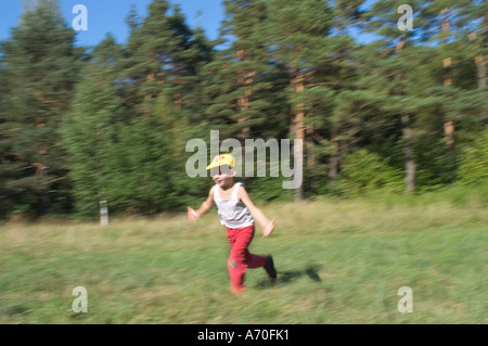 Six year old boy running with outstretched arms - Stock Photo