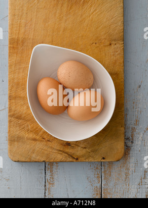 Bowl of eggs on wooden chopping board and blue background - high end Hasselblad 61mb digital image - Stock Photo