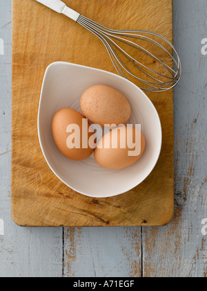 Eggs in white bowl with whisk on wooden board - high end Hasselblad 61mb digital image - Stock Photo