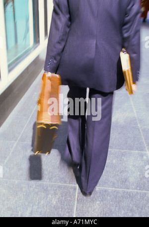 New York City Executive businessman with a briefcase and papers under his arm walking home after work - Stock Photo