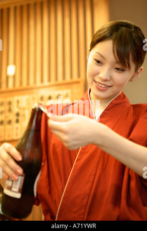 Waitress opening beer bottle - Stock Photo