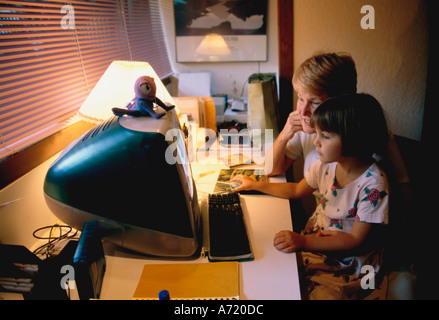 Grandmother and granddaughter working on a MacIntosh computer in a dimly lit room - Stock Photo