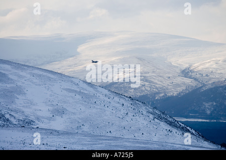 Military jet flying low over Cairngorm Mountains Scotland - Stock Photo