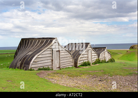 Ancient Upcycled Wooden Upturned Herring Boat shelter made from stern hulls; a weather shed landmark at Lindisfarne - Stock Photo