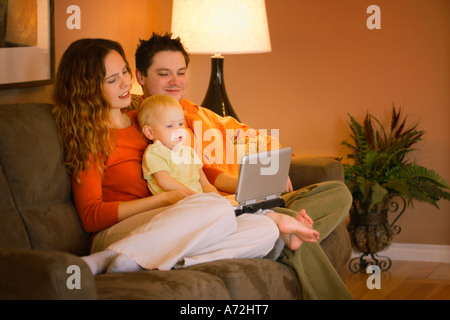 Young family watching movie on portable DVD player - Stock Photo