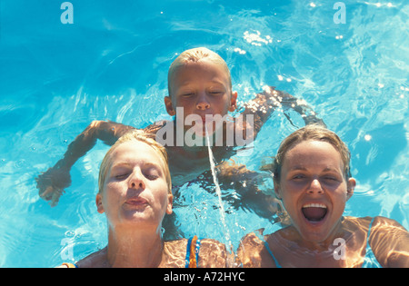 Two young Women and one child in Swimmingpool - Stock Photo