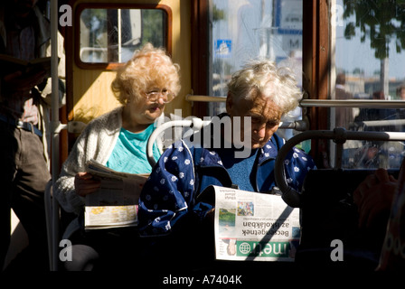 two old women travelling in a tram at budapest One watching through the window and the other reading a free newspaper - Stock Photo