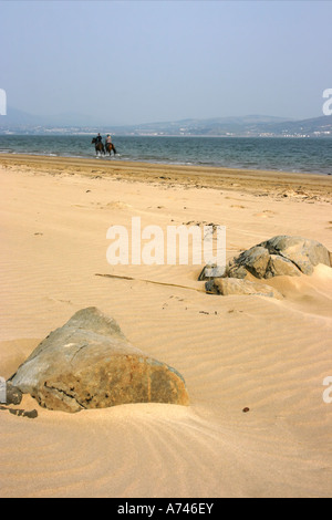 horses and riders in the distance on the beach at Rathmullen, County Donegal, Republic of Ireland - Stock Photo
