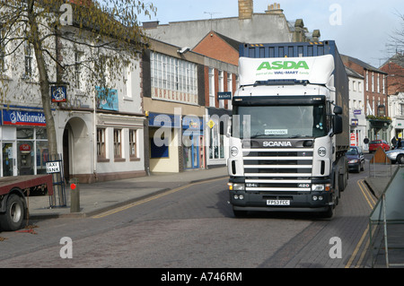 Large lorry driving through a small market town in the uk - Stock Photo