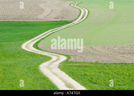 winding road uphill in farmland Ebersberg Upper Bavaria Germany Europe - Stock Photo