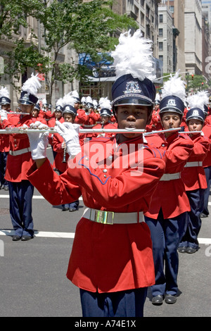 member of a high school band plays the flute as he marches down Madison Avenue in New York City - Stock Photo