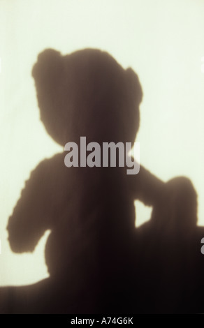Shadow in warm light on pale cloth or curtain of seated teddy bear with big feet looking as if thinking or watching - Stock Photo