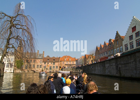 Horizontal view of tourists enjoying a guided boat trip along the canals of Bruges on a bright sunny day. - Stock Photo