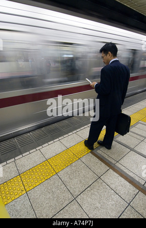 A businessman waits on a subway platform Tokyo Japan - Stock Photo
