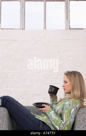 side view of young woman relaxing on armchair drinking cup of tea - Stock Photo