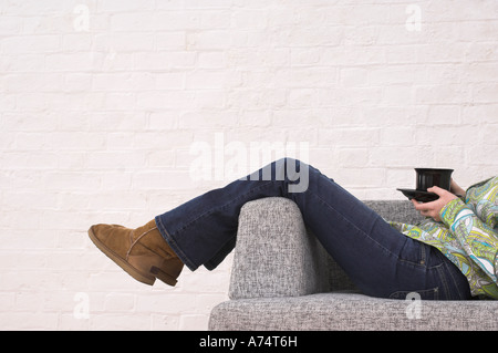 legs of woman taking a rest on armchair holding cup of tea - Stock Photo