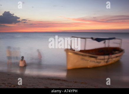 People In Sea Next To Boat At Sunset - Stock Photo