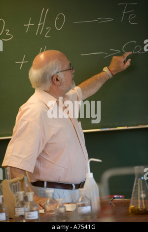 Science teacher demonstrating with chalkboard - Stock Photo