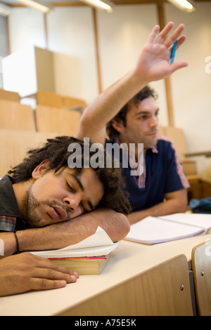 Male student sleeping in class - Stock Photo