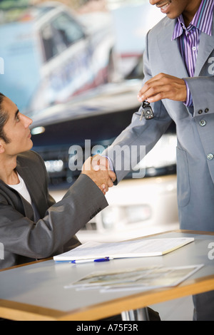 Man shaking hands with car salesman - Stock Photo