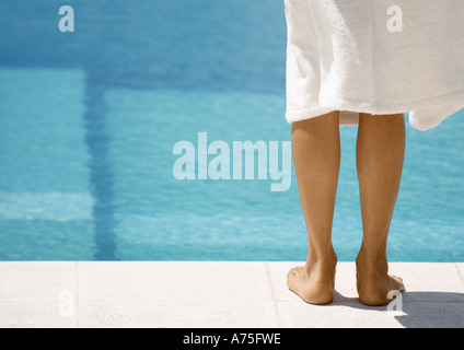 Woman wearing bathrobe standing by side of pool, rear view of legs - Stock Photo