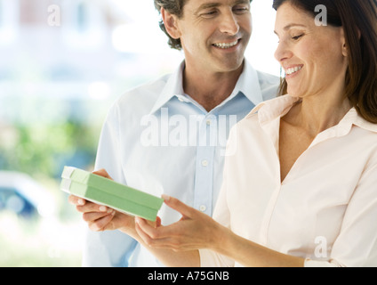 Mature couple, man handing woman gift - Stock Photo