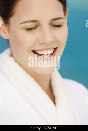 Woman wearing bathrobe, smiling with eyes closed - Stock Photo
